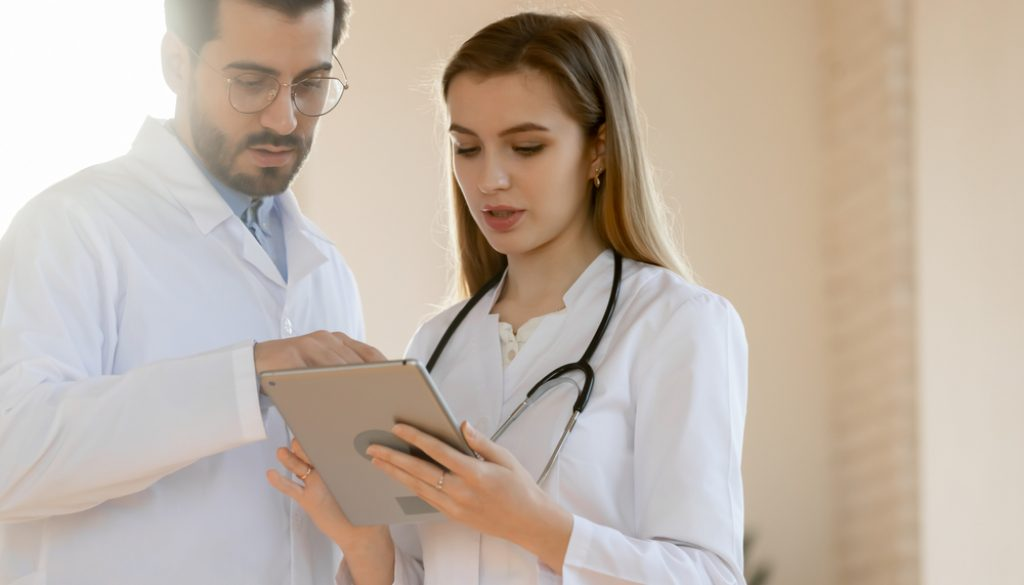 Two,Diverse,Doctors,In,White,Medical,Uniforms,Look,At,Tablet